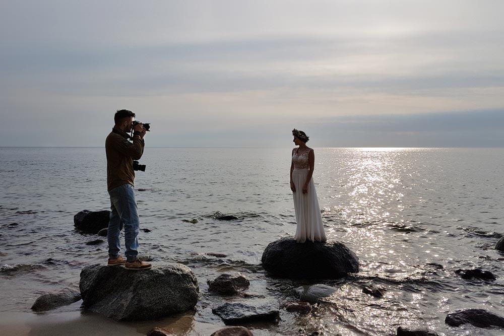 Fotograf ślubny podczas pracy przy sesji nad morzem